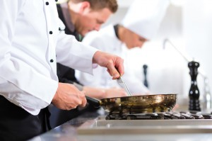 Three chefs in team in hotel or restaurant kitchen