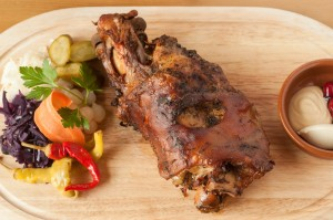 Roasted european pork knuckle on wood platter with vegetable garnish.