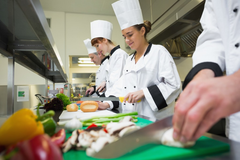 Four chefs preparing food at counter in a row in a professional kitchen